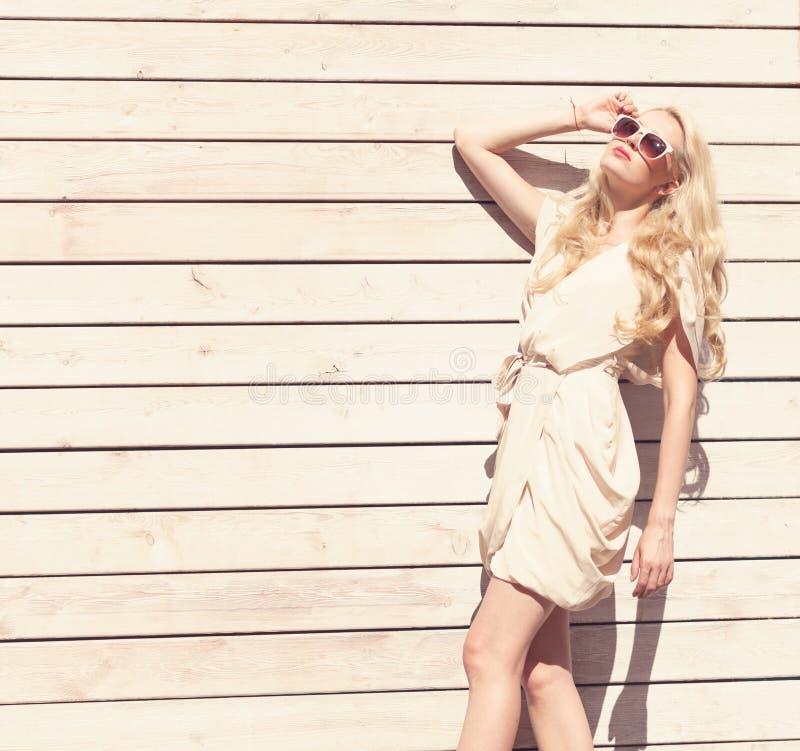 Openlucht het portret mooie jonge blonde vrouw van de de zomer sensuele manier een witte kleding die zich op de achtergrond van h royalty-vrije stock foto