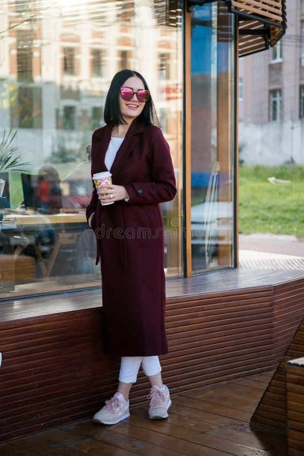 In openlucht het portret van de levensstijlmanier van het overweldigen van donkerbruin meisje Het glimlachen, het drinken koffie  royalty-vrije stock foto