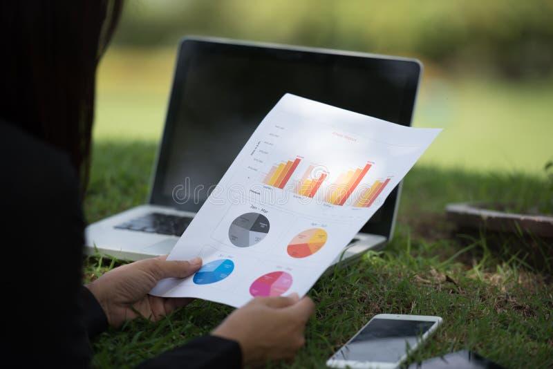 In openlucht het werken aan laptop Bebouwd beeld van wijfje die aan laptop werken terwijl het zitten in een park stock foto