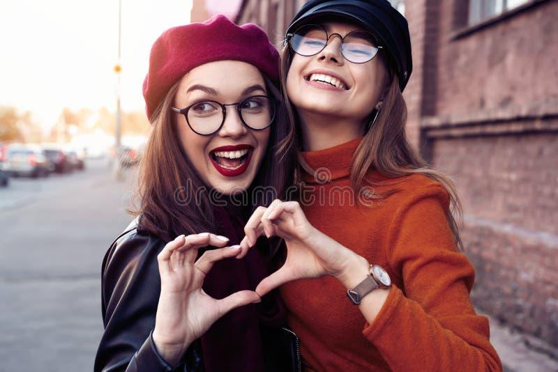 In openlucht jonge vrij beste de meisjesvrienden van het manierportret in vriendschappelijke omhelzing Het lopen bij de stad Het  stock foto