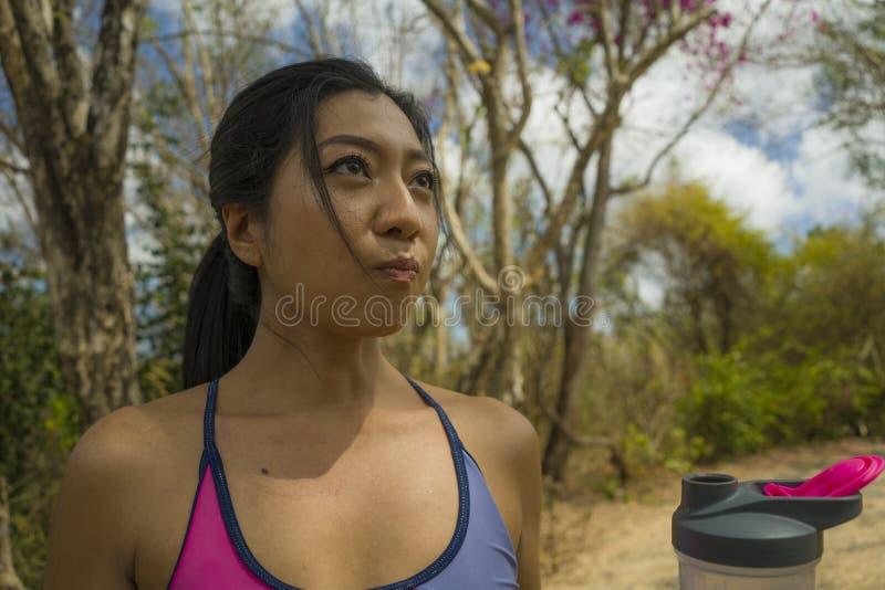In openlucht levensstijlportret van jong aantrekkelijk vermoeid en dorstig Aziatisch vrouwen drinkwater na het harde lopende trai stock fotografie