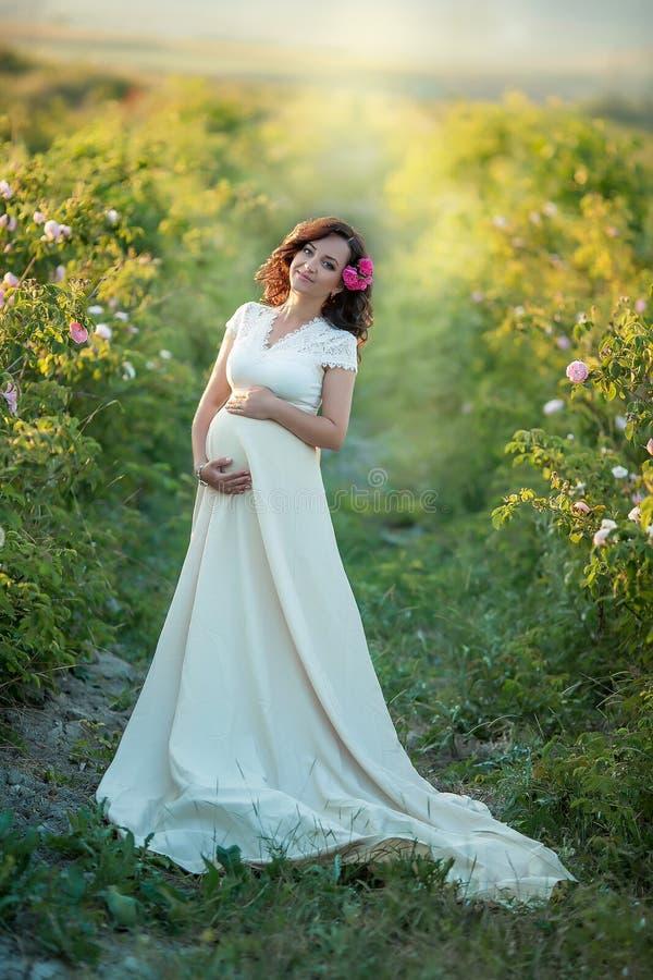 Openlucht natuurlijk portret van mooie zwangere vrouw in witte kleding royalty-vrije stock afbeeldingen