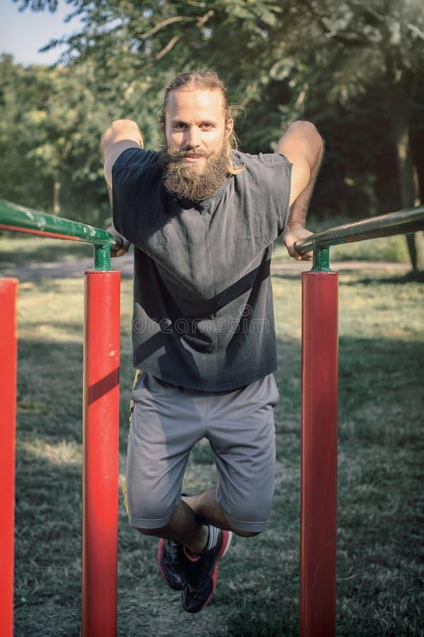 In openlucht opleiding Mens die bicepsen en tricepsonderdompelingen opleiding doen royalty-vrije stock fotografie