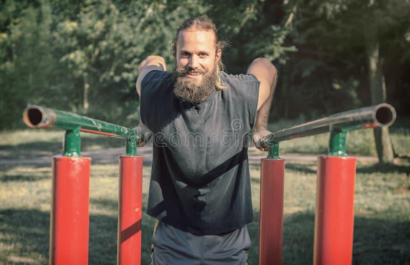 In openlucht opleiding Mens die bicepsen en tricepsonderdompelingen opleiding doen stock afbeelding