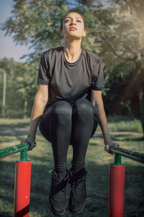 In openlucht opleiding Mooie vrouw die bicepsen en tricepsonderdompelingen doen royalty-vrije stock foto's