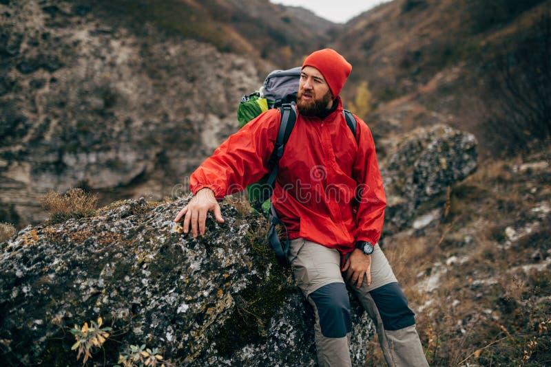 In openlucht portret van de vermoeide wandelaarmens die in rode kleren op rots het ontspannen na wandeling in berg zitten royalty-vrije stock afbeeldingen