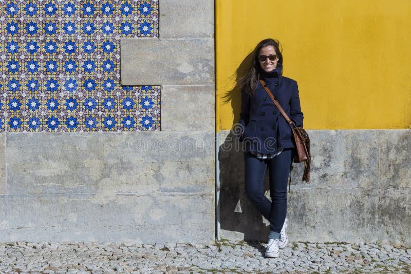 In openlucht Portret van een jonge mooie vrouw over gele muurbedelaars stock afbeelding