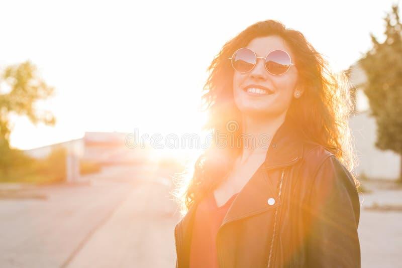 In openlucht portret van een mooie jonge vrouw die bij zonsondergang m dragen royalty-vrije stock fotografie