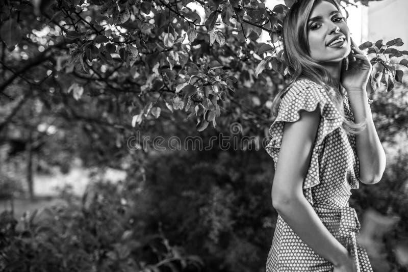 In openlucht portret van het mooie jonge vrouw stellen in de herfsttuin Zwart-witte foto stock fotografie