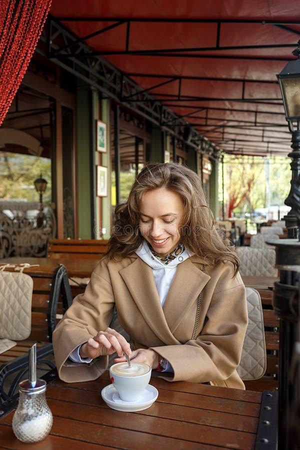 In openlucht portret van jong glimlachend meisje die beige laag het drinken koffie op de stiring suiker van de koffieveranda met  stock foto