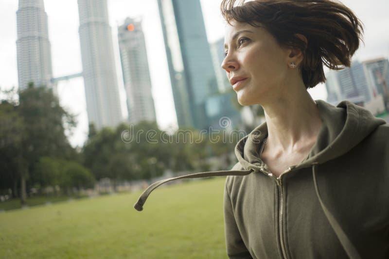 In openlucht portret van jonge aantrekkelijke en actieve joggervrouw in hoodie het hoogste lopen en het aanstoten in ochtendtrain stock afbeelding