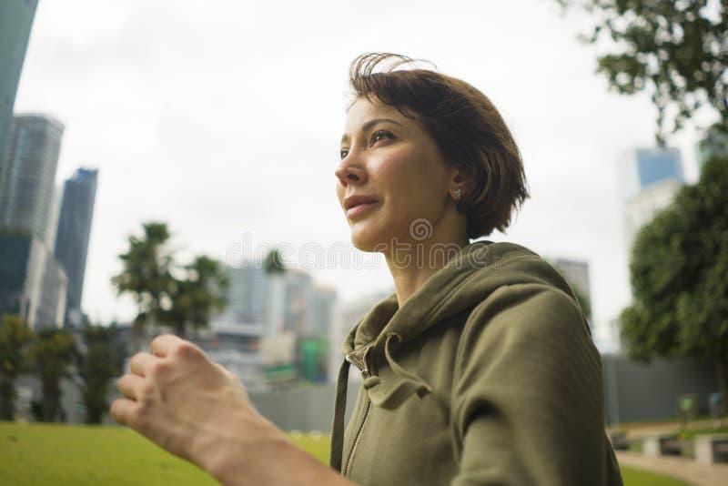 In openlucht portret van jonge aantrekkelijke en actieve joggervrouw in hoodie het hoogste lopen en het aanstoten in ochtendtrain stock afbeeldingen