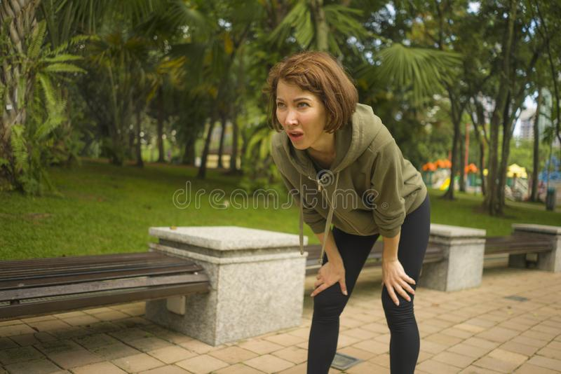 In openlucht portret van jonge aantrekkelijke vermoeide en ademloze joggervrouw in ademhaling uitgeput na het runnen van training stock foto