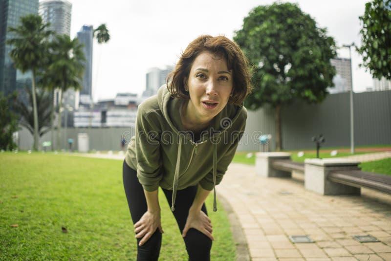 In openlucht portret van jonge aantrekkelijke vermoeide en ademloze joggervrouw in ademhaling uitgeput na het runnen van training stock afbeeldingen