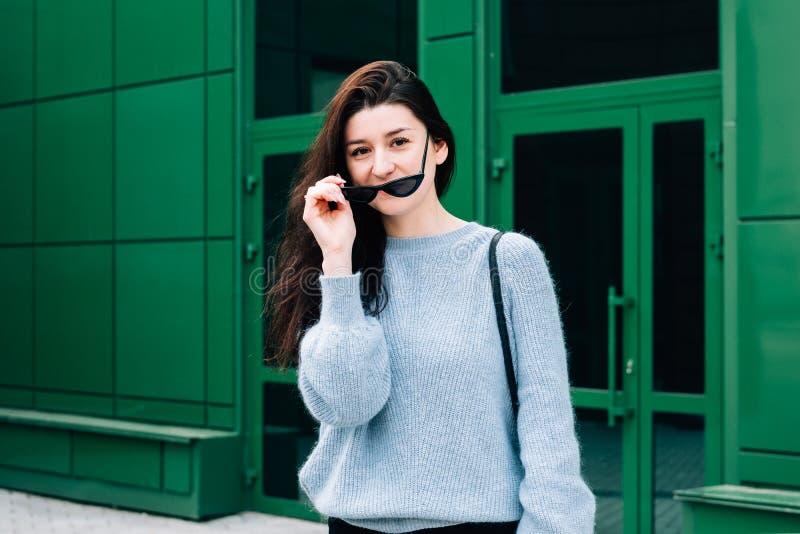 In openlucht portret van mooi jong donkerbruin meisje Tienerglamourmeisje met zonnebril die het in uitrusting stellen in stad dra royalty-vrije stock foto