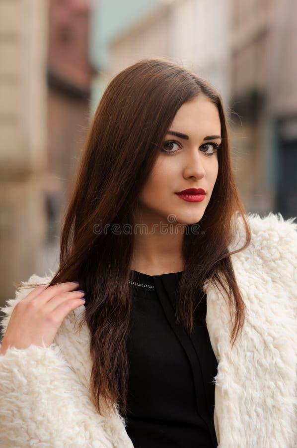In openlucht portret van mooie jonge vrouw met grote ogen en rood royalty-vrije stock fotografie
