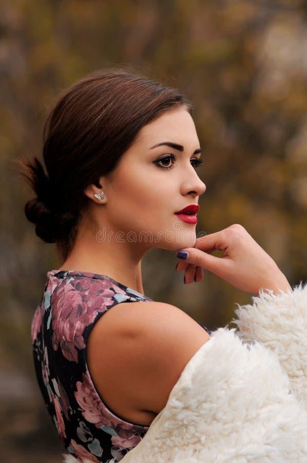 In openlucht portret van mooie jonge vrouw met grote ogen en rood stock afbeelding