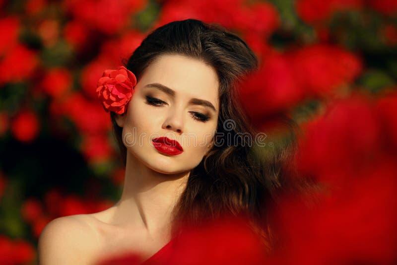 In openlucht portret van Natuurlijke Schoonheidsvrouw in rode rozen Sensueel stock fotografie