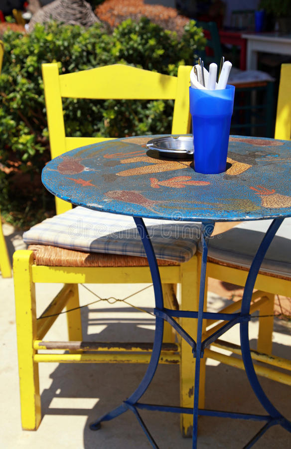 Openlucht restaurant met blauwe lijst en gele stoel (Griekenland) stock fotografie