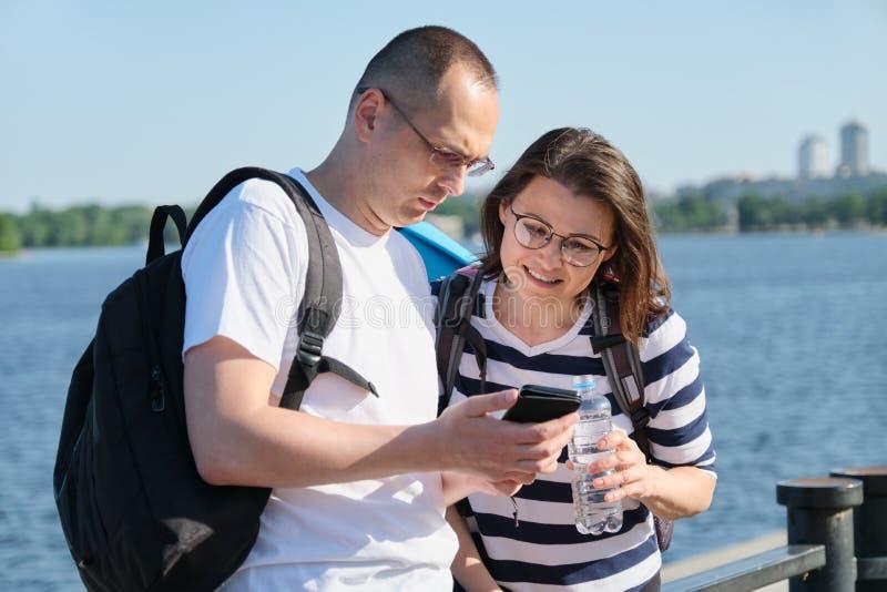 Openlucht rijp paar die smartphone, man en vrouwen spreken gebruiken die in het park lopen stock foto's