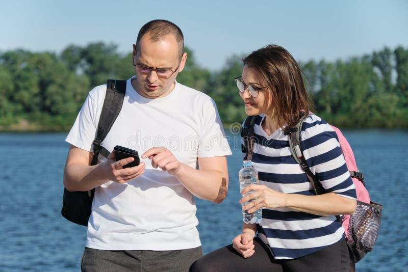Openlucht rijp paar die smartphone, man en vrouwen spreken gebruiken die in het park lopen stock afbeeldingen