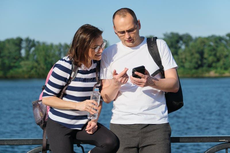 Openlucht rijp paar die smartphone, man en vrouwen spreken gebruiken die in het park lopen stock foto