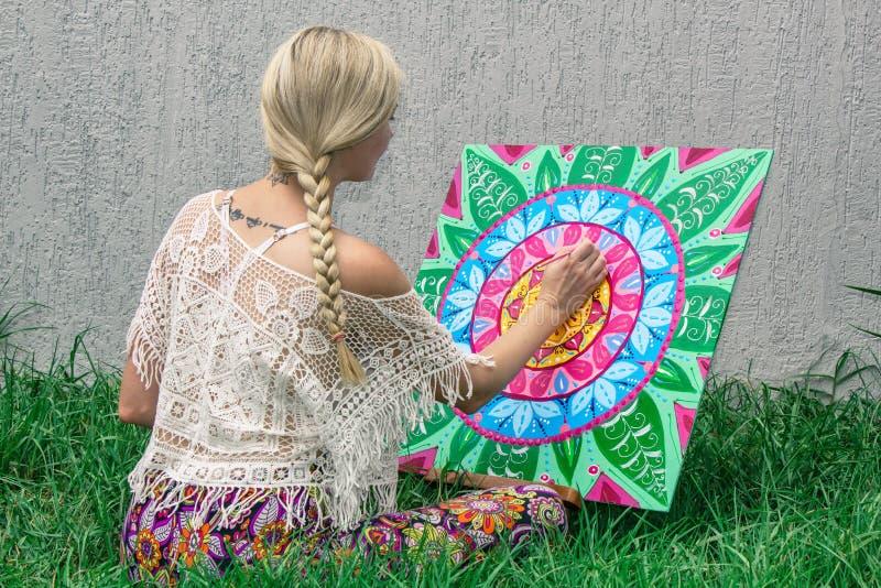 In openlucht schilderend, trekt een jong vrouwenblonde een mandala op de aardzitting in het gras royalty-vrije stock foto