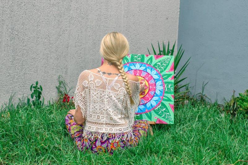 In openlucht schilderend, trekt een jong vrouwenblonde een mandala op de aardzitting in het gras stock fotografie