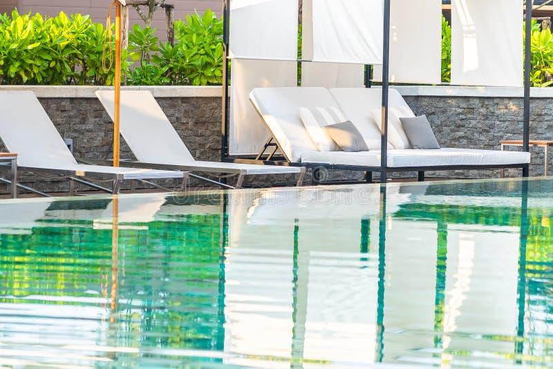 Openlucht zwembad met de zitkamer van de paraplustoel rond daar voor vrije tijdsreis royalty-vrije stock afbeeldingen