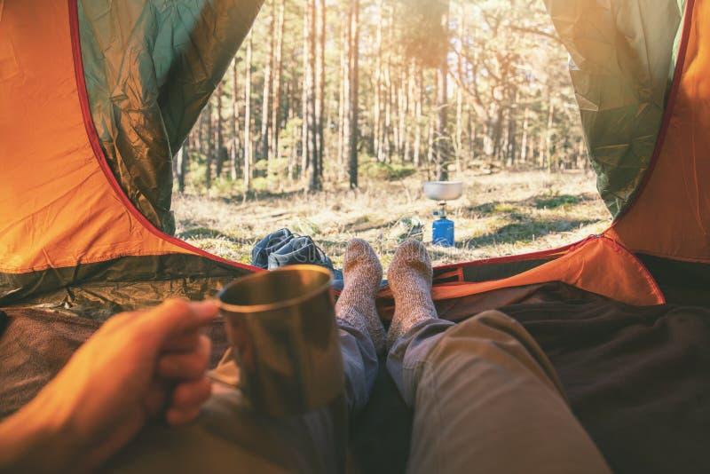 Openluchtavonturentoerisme - mens die in tent met kop thee leggen royalty-vrije stock fotografie