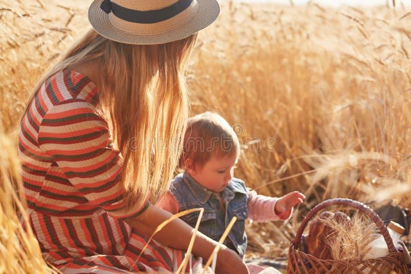 Openluchtbeeld van jonge eerlijke haired moederzitting met haar weinig dochter bij tarwegebied, die kleine picknick hebben samen, stock afbeelding