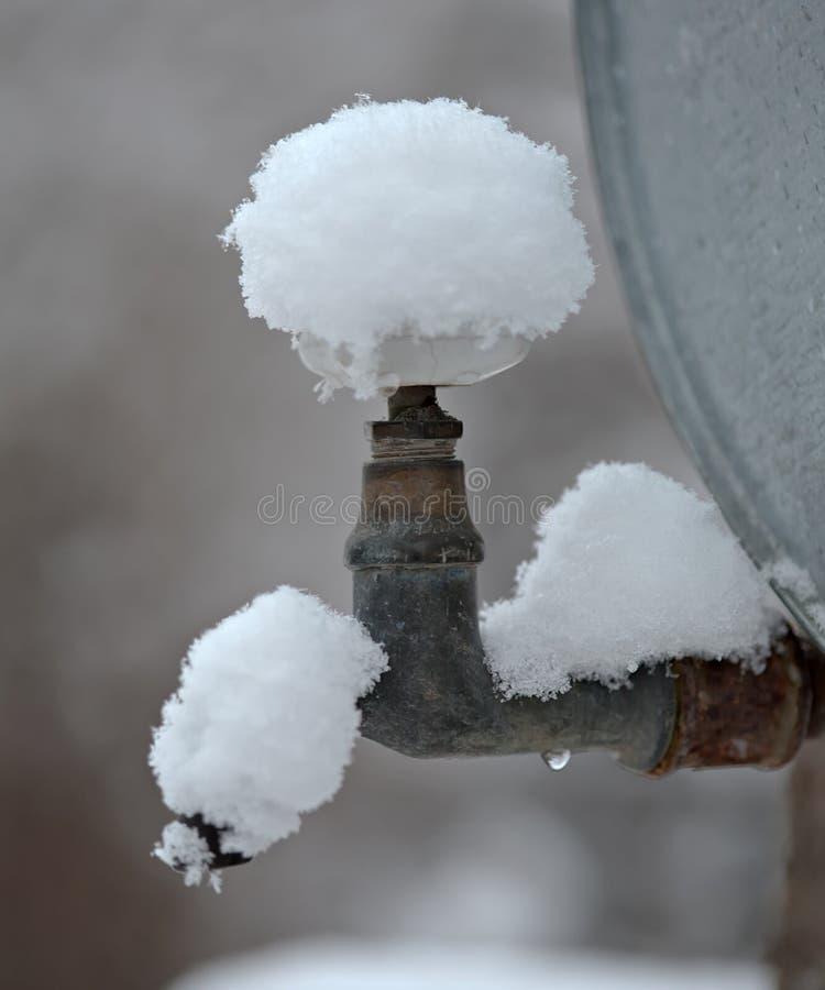 Openluchtdiemetaaltapkraan door sneeuw wordt behandeld royalty-vrije stock foto