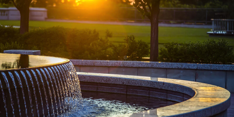 Openluchtfontein met weerspiegelend water bij zonsondergang stock afbeeldingen