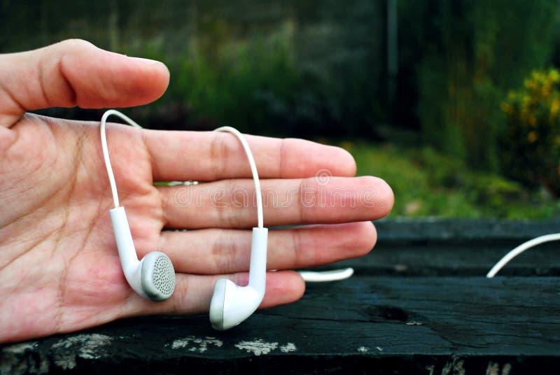 Openluchtfotografie van hand en oortelefoonvoorwerpen bij tuin in de ochtend royalty-vrije stock fotografie