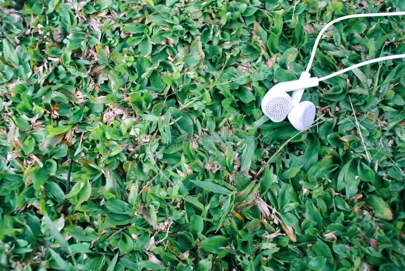Openluchtfotografie van oortelefoonvoorwerp op de grasachtergrond royalty-vrije stock afbeelding