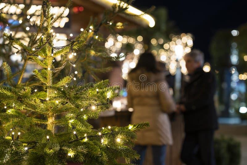 Openluchtkerstmisboom met vage uit mensen die overwogen wijn op Kerstmismarkt drinken in merano Zuid- 's nachts Tirol stock afbeeldingen