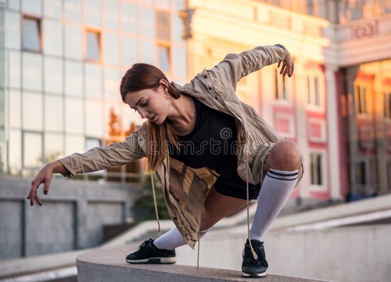 Openluchtlevensstijlbeeld van een jong mooi kastanje haired Kaukasisch meisje die en op de straat stellen dansen Leuke toevallig royalty-vrije stock afbeeldingen
