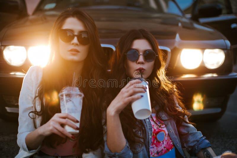 Openluchtlevensstijlportret van een paar die beste vrienden vrij jonge meisjes die zonnebril dragen, een heldere prooi dragen royalty-vrije stock fotografie