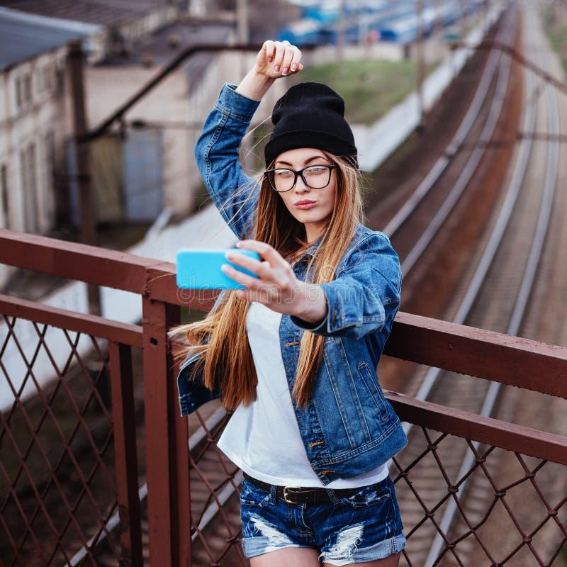 Openluchtlevensstijlportret van het jonge sexy blonde hipster vrouw stellen voor selfie en het lachen Het dragen van jeansjasje,  royalty-vrije stock foto