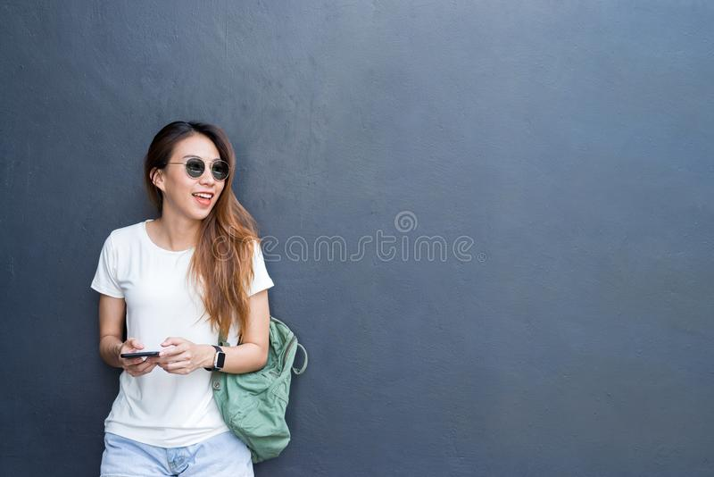 Openluchtlevensstijlportret van vrij sexy jong Aziatisch meisje in reis en glazenstijl op grijze muurachtergrond stock afbeeldingen