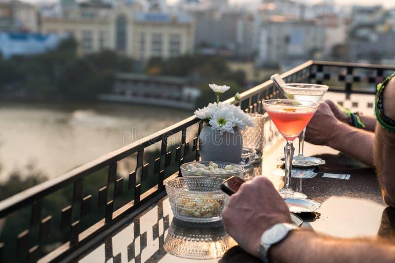 Openluchtlijst in een koffie en bar met een oranje cocktail en mensenhandenclose-up Stedelijk cityscape en meer op achtergrond Br royalty-vrije stock afbeeldingen
