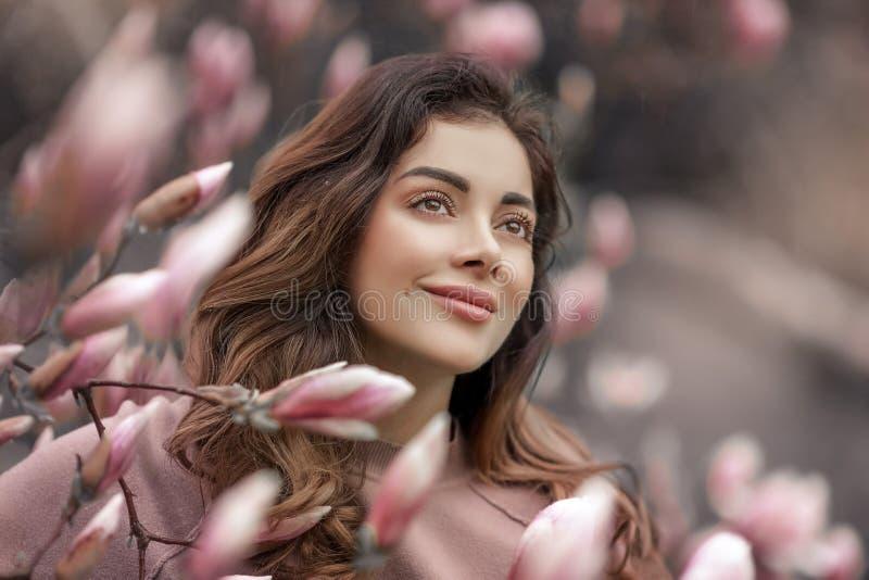 Openluchtmanierfoto van mooie jonge die vrouw door bloemen wordt omringd De Bloesem van de lente stock afbeelding