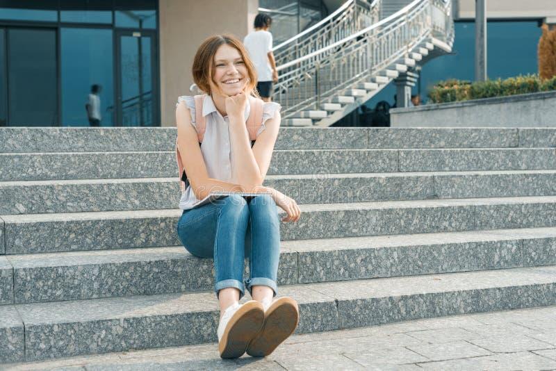 Openluchtportret die van jong mooi glimlachend studentenmeisje met rugzak, op de stappen in de stad zitten royalty-vrije stock fotografie