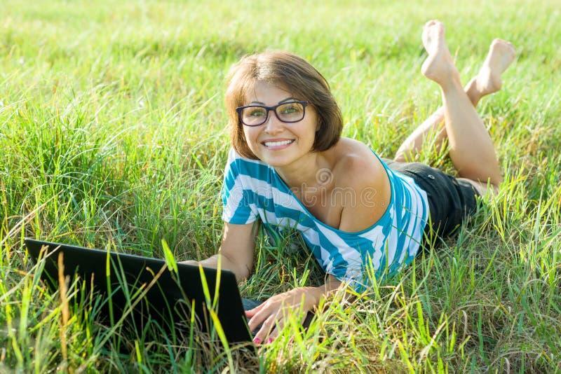 Openluchtportret die vrouwen freelancer blogger reiziger op middelbare leeftijd met laptop op aard glimlachen royalty-vrije stock fotografie