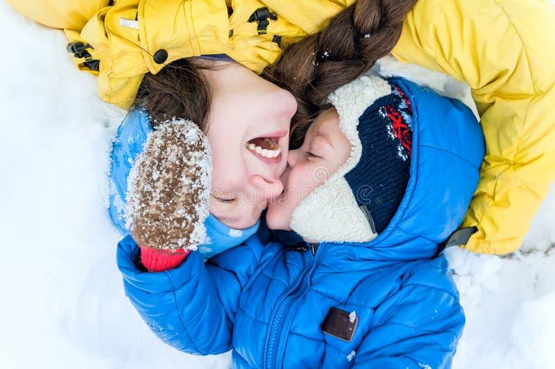 Openluchtportret Gelukkige moeder en baby die op de sneeuw in wint liggen stock fotografie
