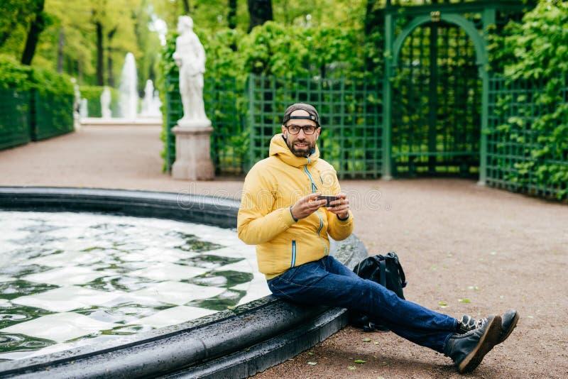 Openluchtportret van de dichtbegroeide mens die GLB, jasje, jeans en oogglazen dragen die rust hebben die dichtbij fontein zijn m stock afbeeldingen