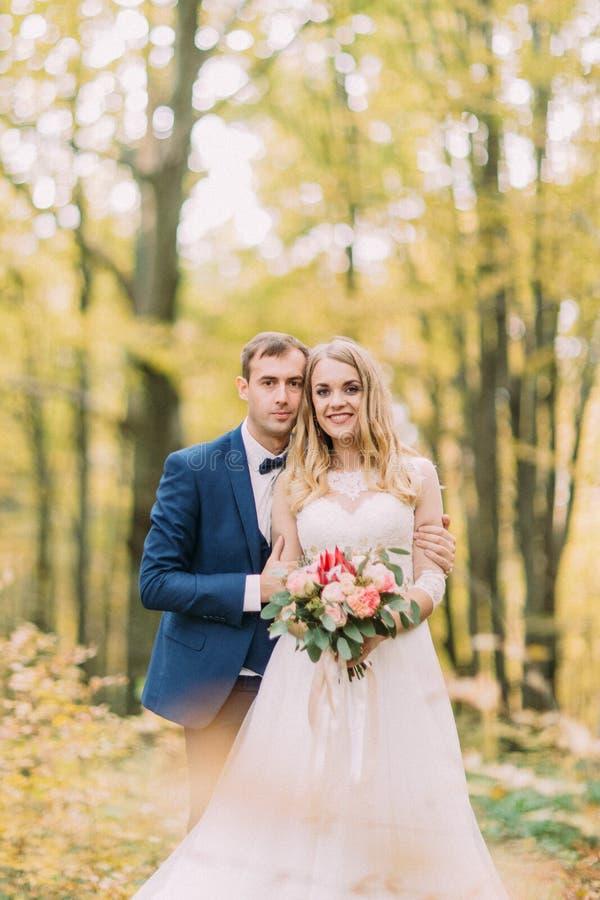 Openluchtportret van de koesterende jonggehuwden in het vergeelde bos stock afbeeldingen