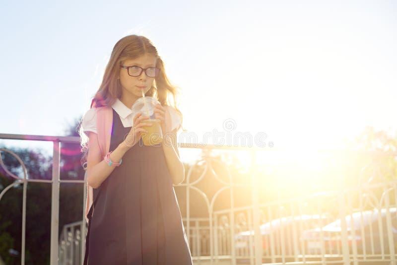 Openluchtportret van de student die van de meisjes basisschool glazen, school dragen eenvormig, met rugzak die natuurlijk sap dri royalty-vrije stock afbeeldingen