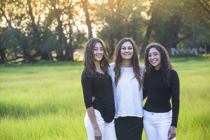 Openluchtportret van drie mooie Spaanse vrouwen die zich in openlucht verenigen royalty-vrije stock foto
