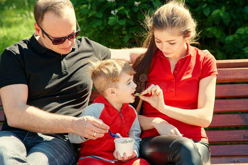 Openluchtportret van een gelukkige familie Mamma, papa en kind die roomijs eten stock afbeelding